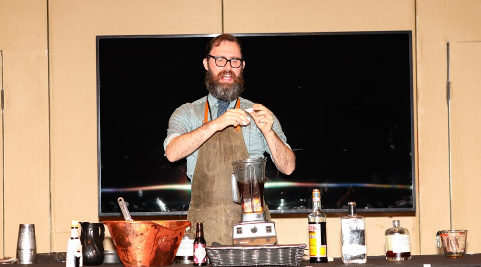 man showing how to make mixed whiskey drinks